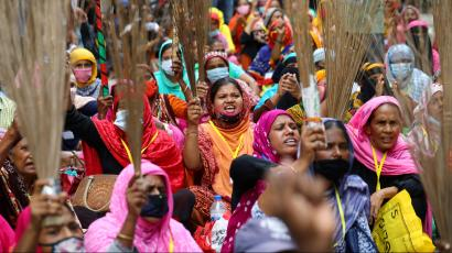 Garment workers shout slogans while holding brooms during a protest demanding their due wages in Dhaka, Bangladesh