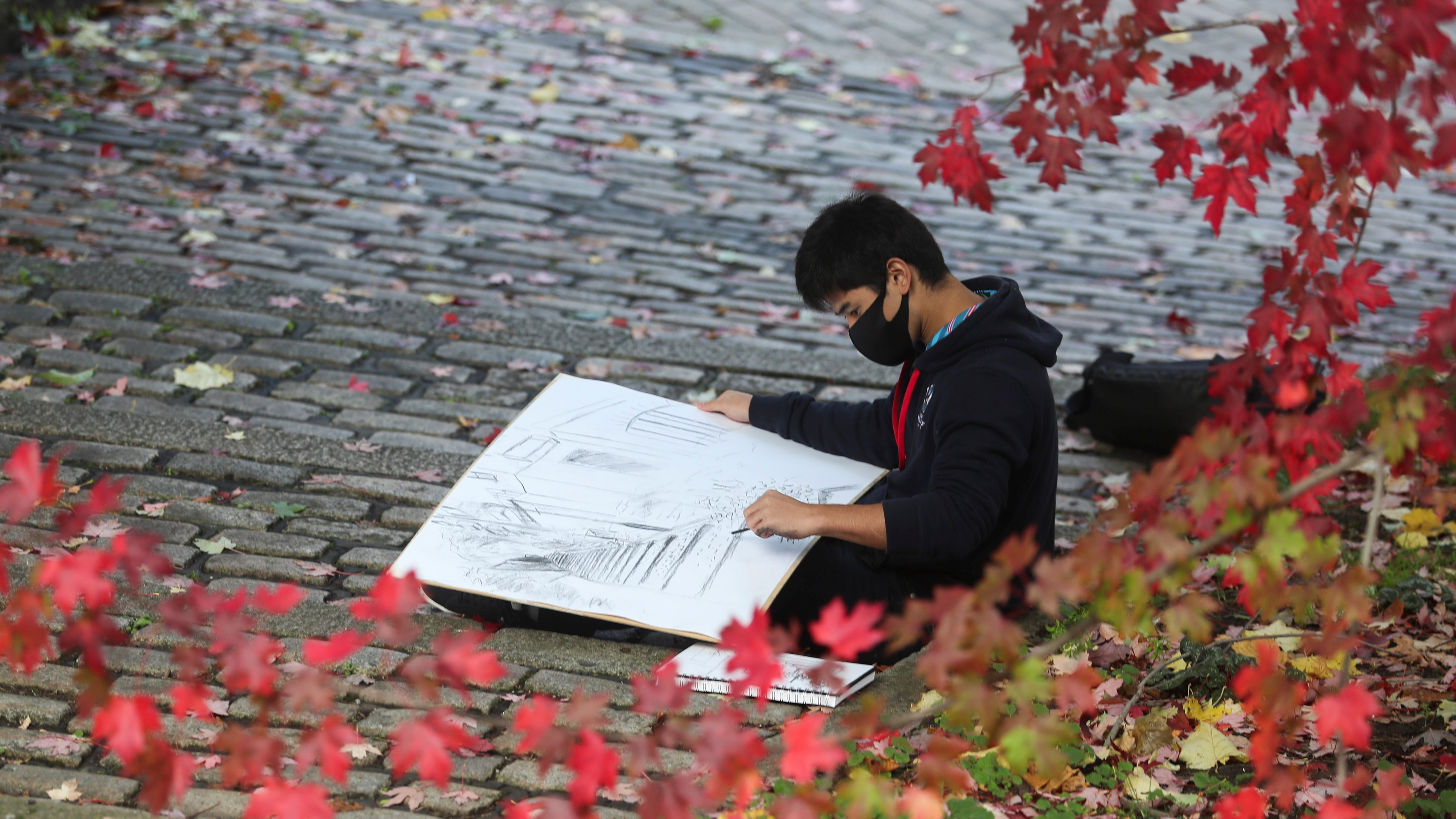 First year architecture student Shuntaro Moyiyama from Japan draws during his first contact with the Newcastle University since he joins over a week ago at Quayside in Newcastle, Britain October 14, 2020. REUTERS/Lee Smith