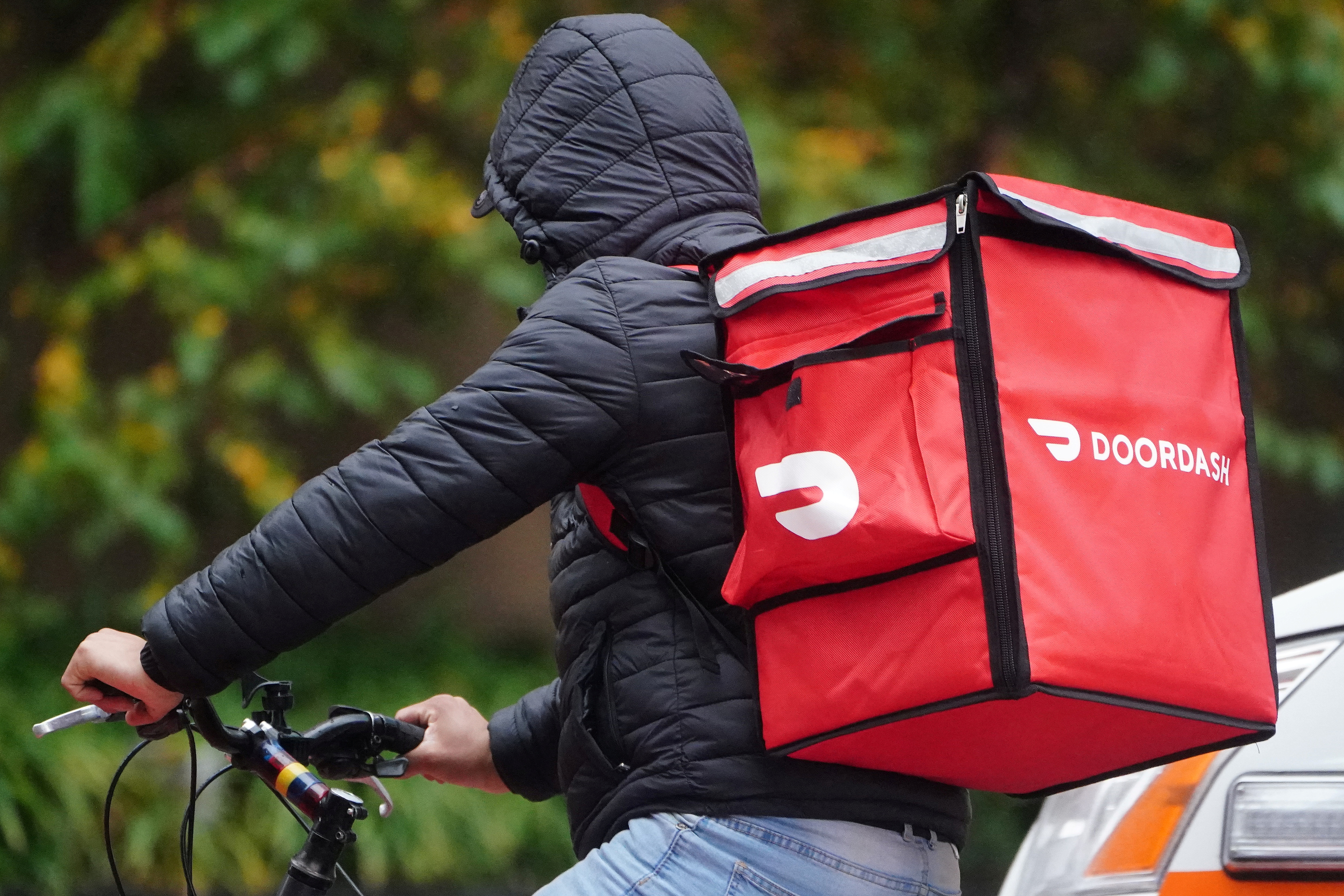 A delivery person for Doordash rides his bike in the rain in the Manhattan borough of New York City