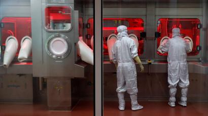 Two lab employees wearing full white jumpsuits, hoods, shoe coverings and gloves stand in front of a lab filling machine at the Serum Institute of India. One employee has his arms inside rubberized inserts while another peers into the window, lit by red light.