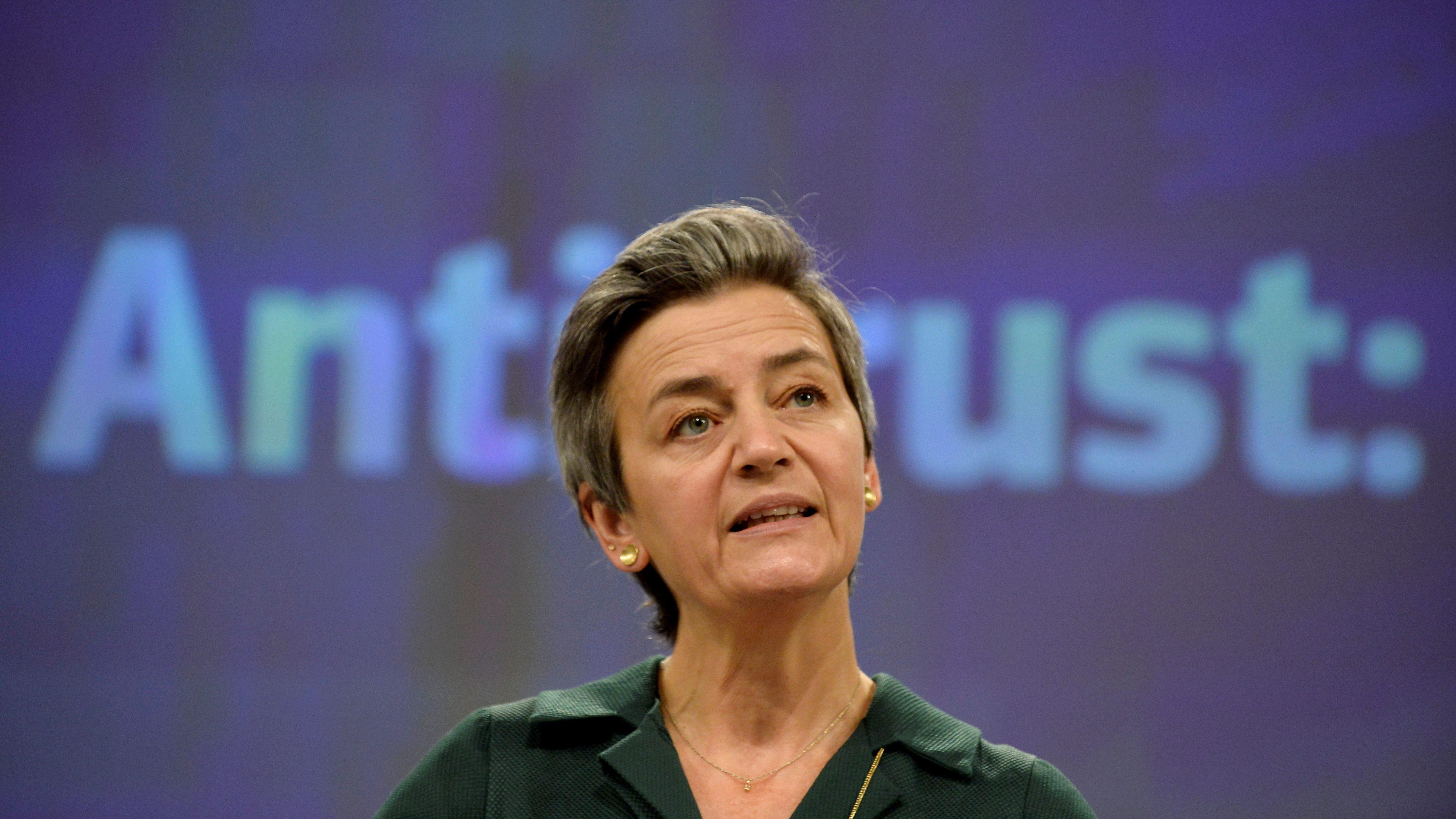 EU competition czar Margrethe Vestager speaks in front of a backdrop that says antitrust.