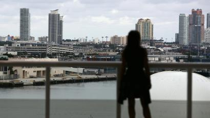 A woman stands on the balcony overlooking the offices of downtown Miami.