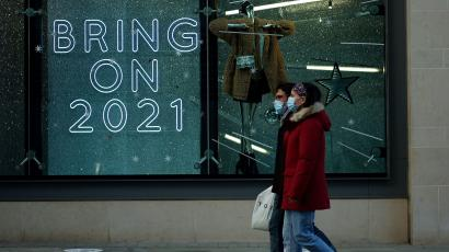 "Two people, wearing blue disposable masks, walk past a store with a neon window sign that says ""bring on 2021"" in large capital letters."