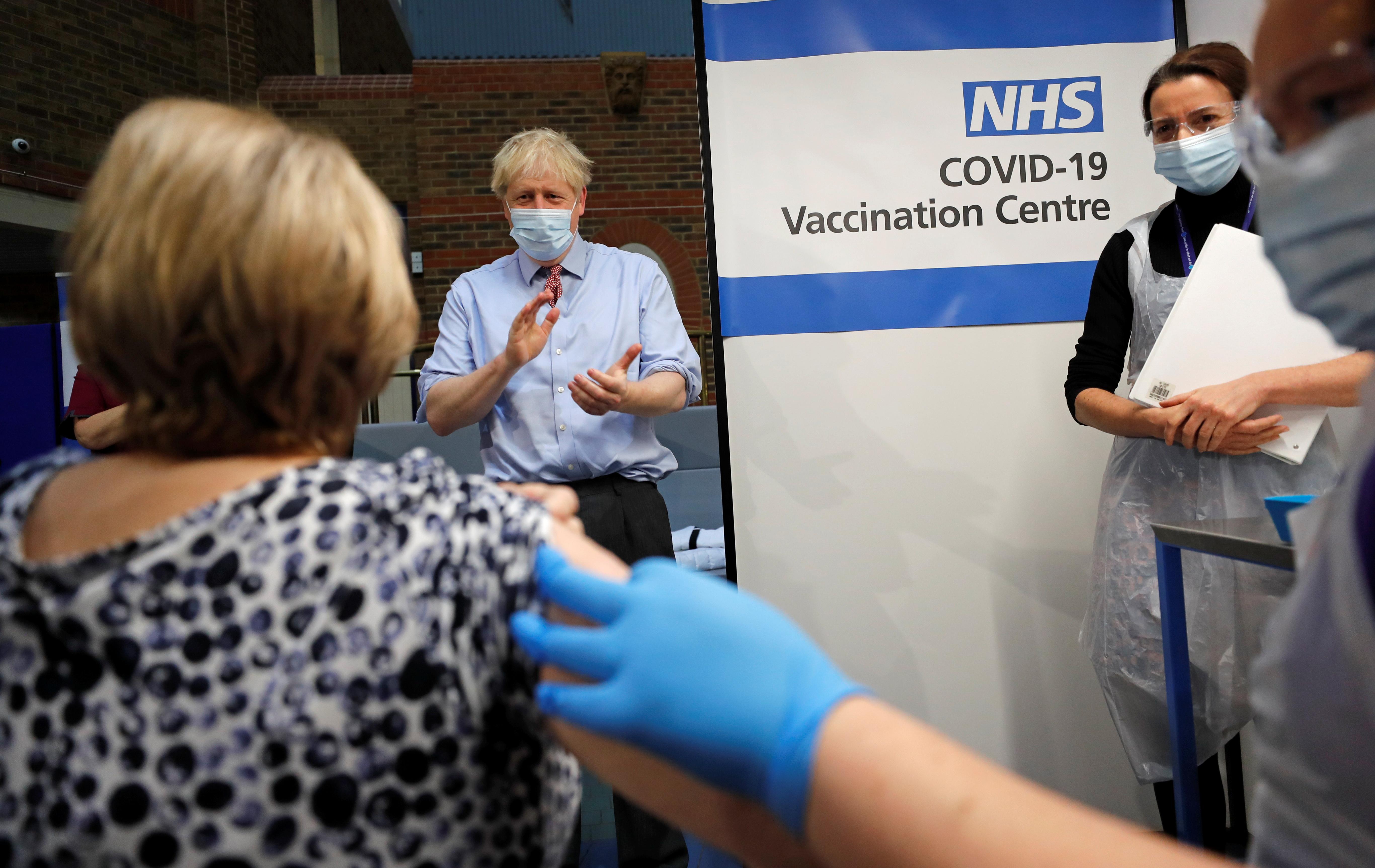 British prime minister Boris Johnson claps after a nurse administers the Pfizer/BioNTech Covid-19 vaccine.