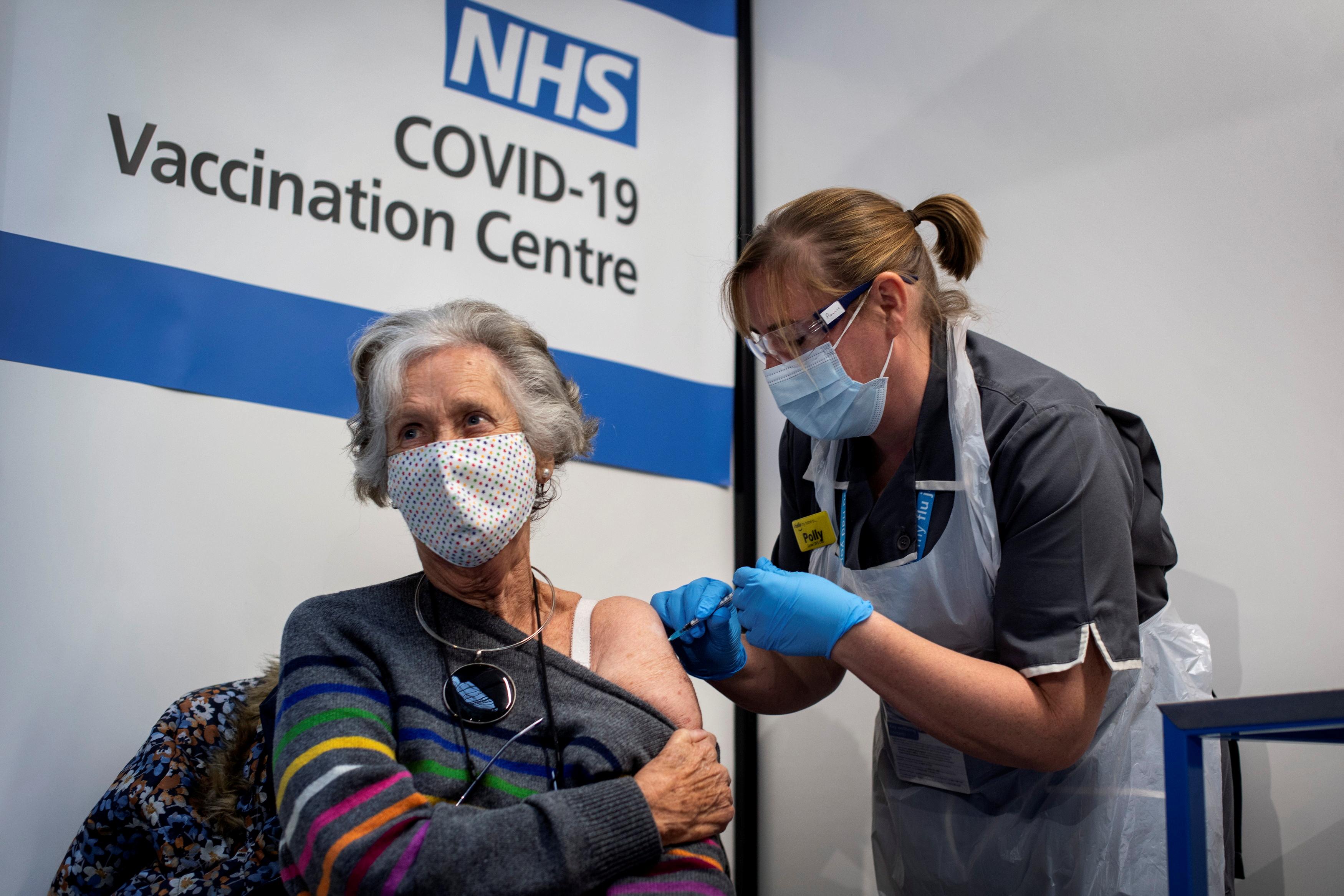 یک پرستار واکسن Covid-19 را به یک زن مسن تزریق می کند.