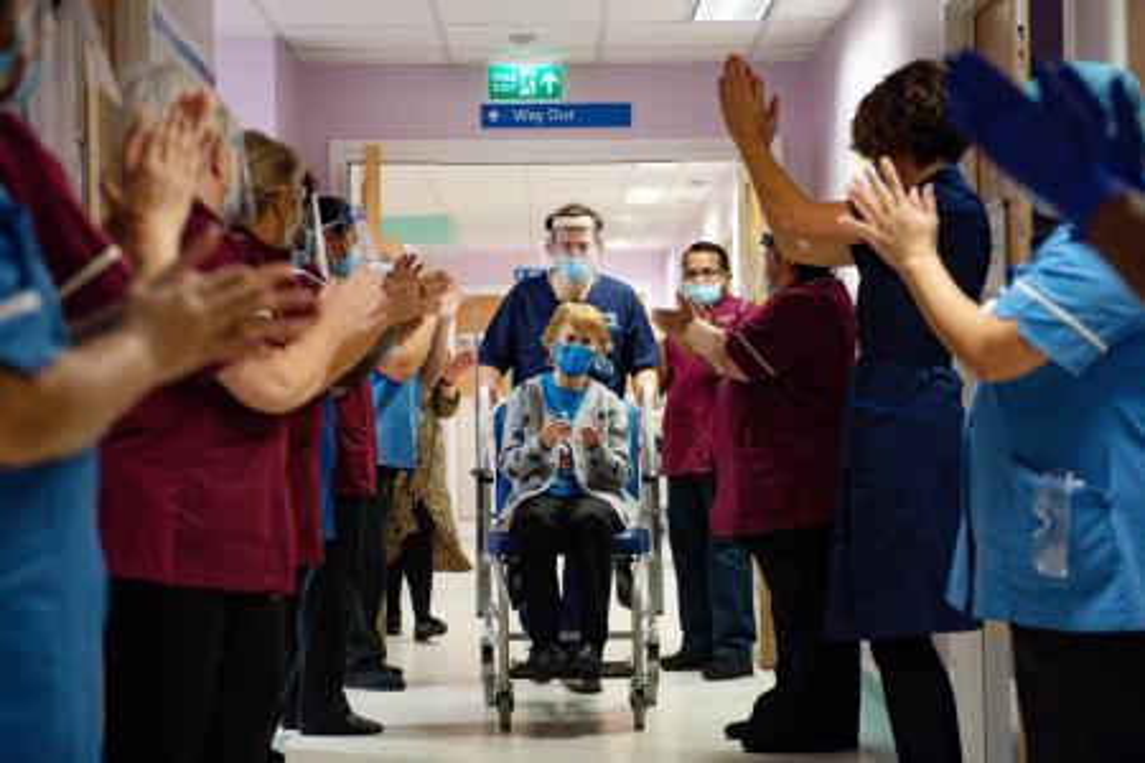 Staff applauds Margaret Keenan on her wheelchair