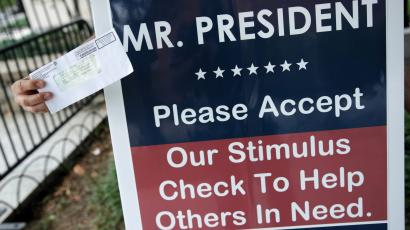 """A hand outstretched holds a stimulus check in front of a sign that reads: """"Mr. President, please accept our stimulus check to help others in need."""""""