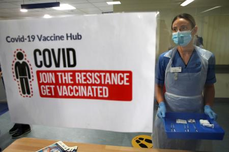 """Deputy charge nurse Katie McIntosh stands in front of a sign that reads, """"Join the resistance, get vaccinated."""""""