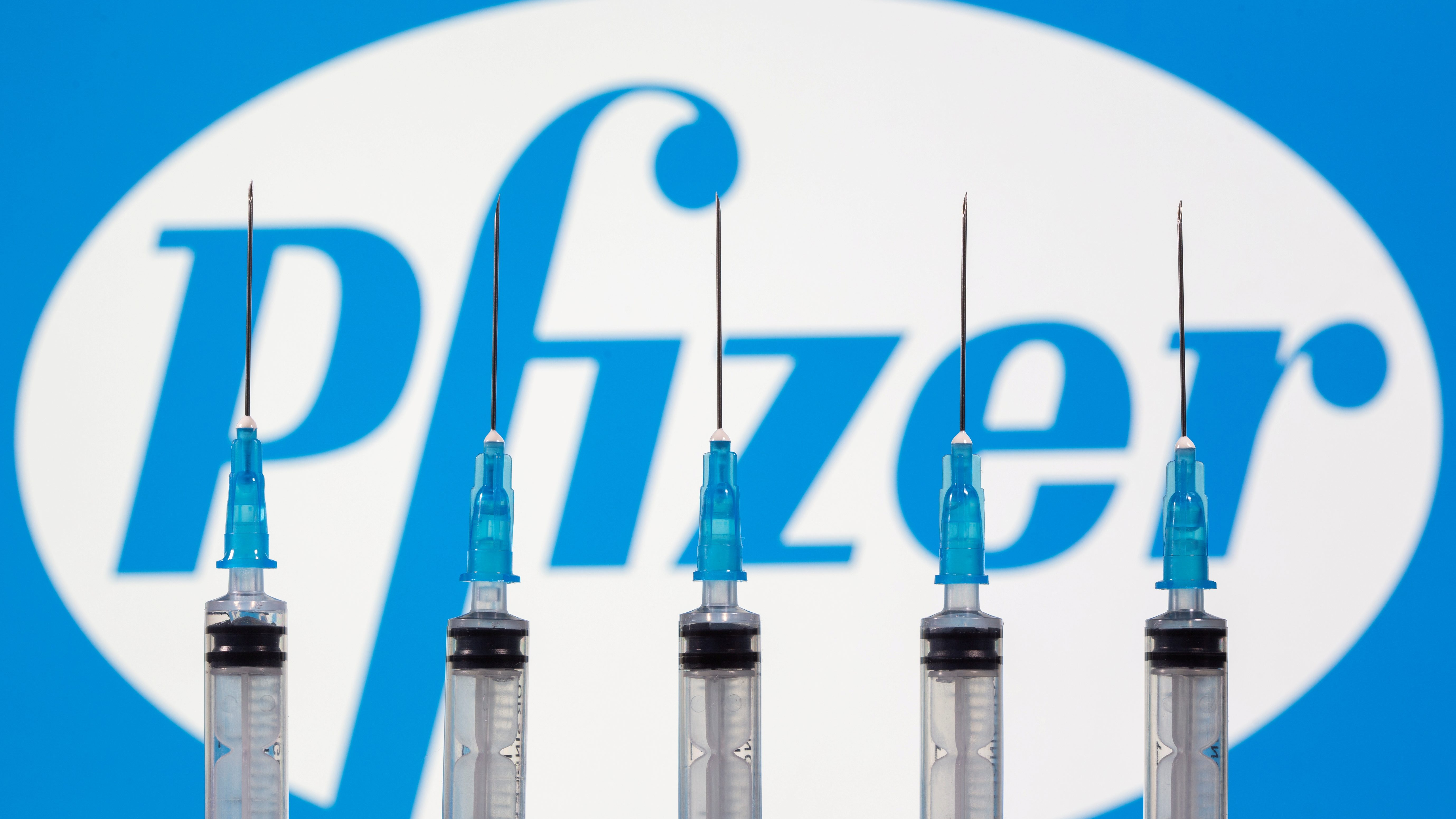 Syringes are seen in front of a Pfizer logo
