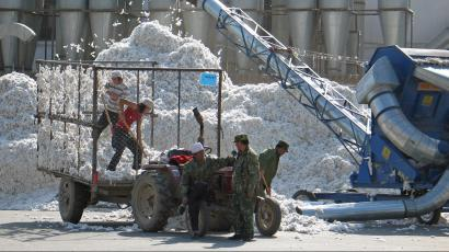 Chinese workers prepare recently picked cotton at a processing plant in Shihezi, Xinjiang