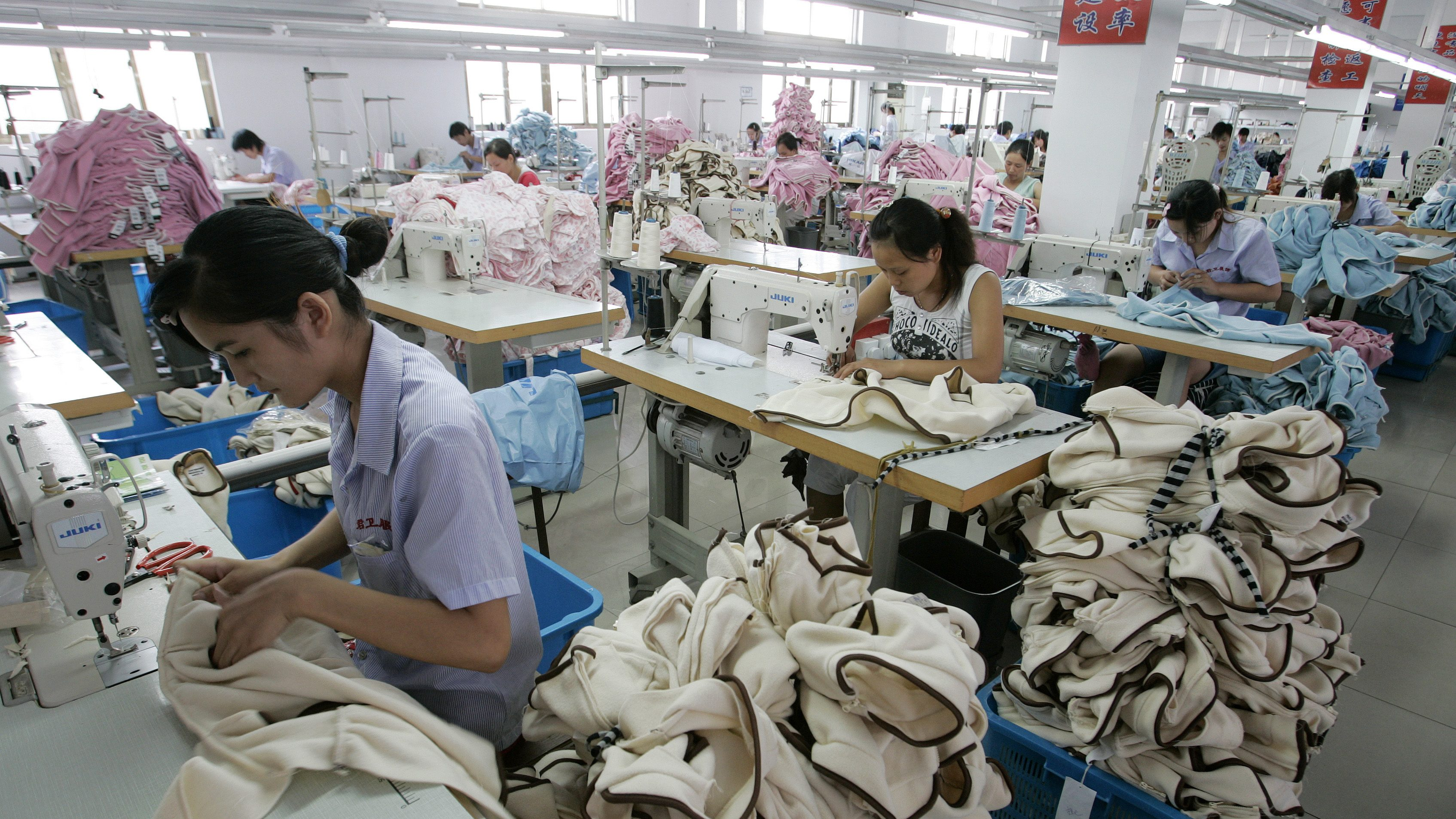 Labourers work on garments for export at the production line of a garment factory in Shanghai