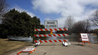 A road covered in water is closed off to traffic in the Burke Addition neighborhood of Grand Forks, North Dakota April 13, 2011.