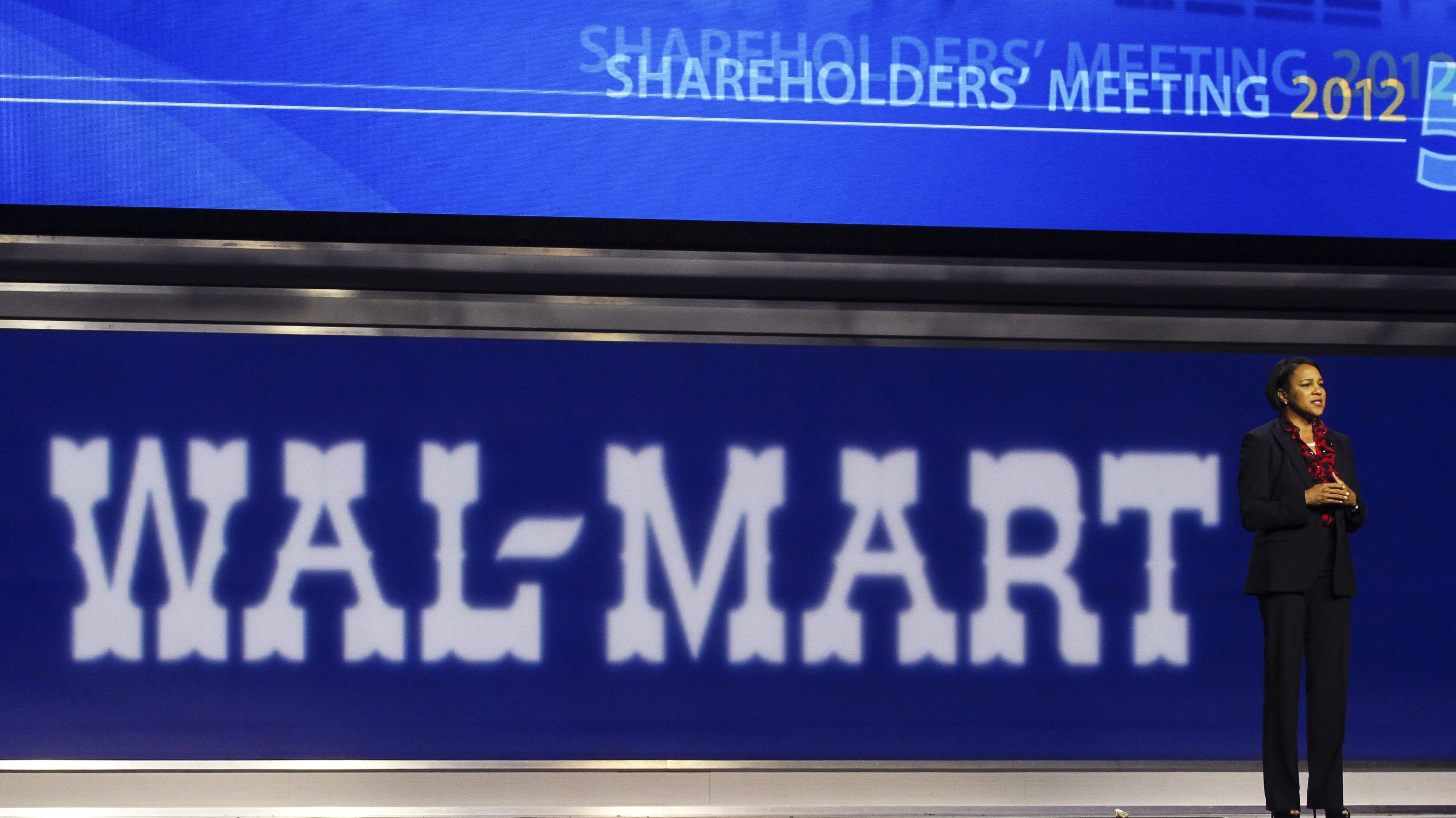 Sam's Club CEO Rosalind Brewer stands in front of a large, dark blue Wal-Mart sign during the company's annual shareholders' meeting.