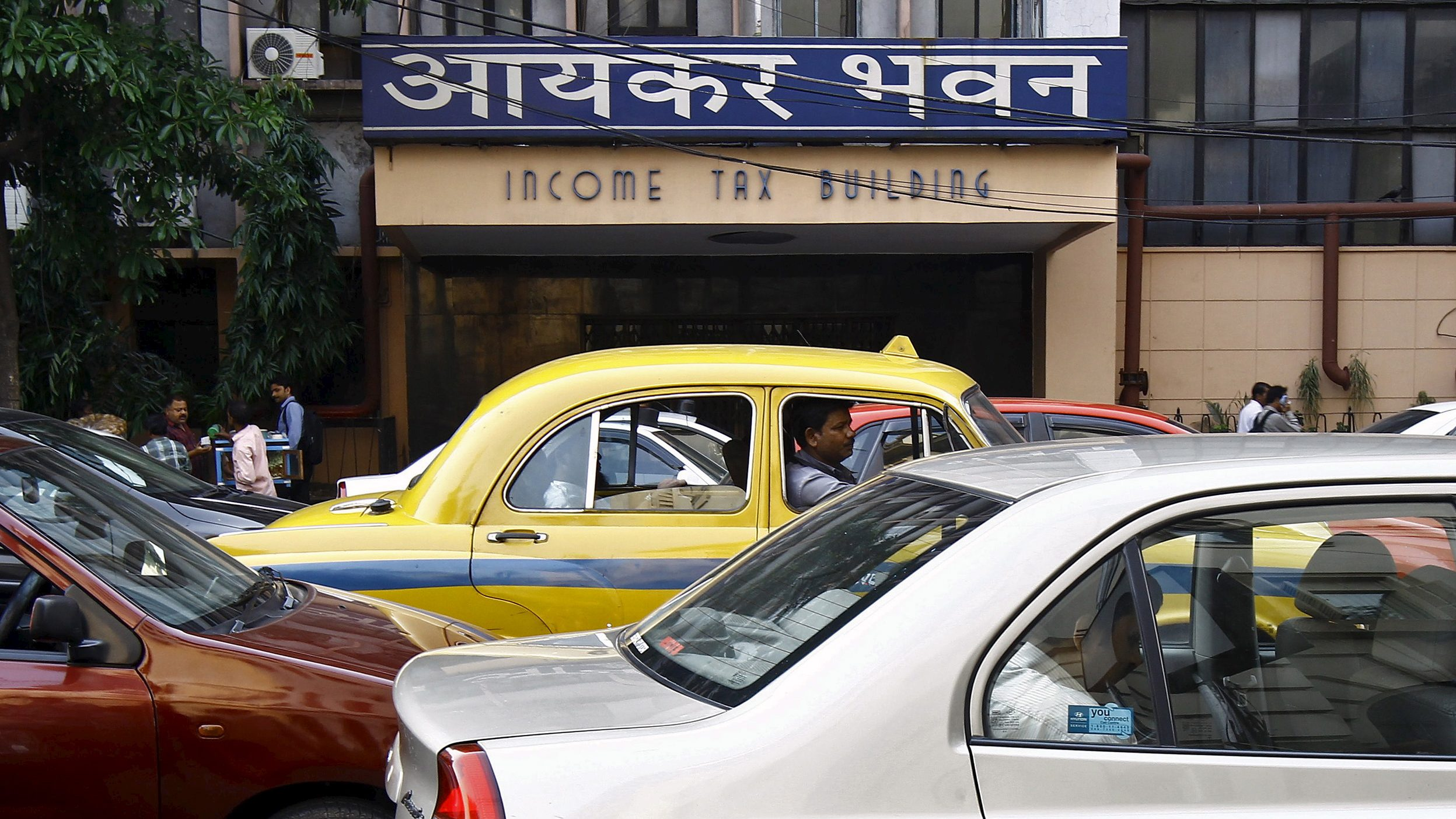 Commuters sit in cars in front of the income tax building during a traffic jam in Kolkata