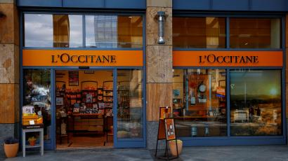 A storefront of the French beauty company L'Occitane en Provence is shown with its glass doors open and items displayed on a small table to the left.