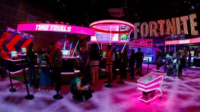 """A neon pink sign says """"Free Trials"""" in all-caps in white letters while a larger sign saying Fortnite is in the background at the Epic Games booth at the E3 convention. A shopping cart outfitted with neon pink lights is also in the lower right corner."""
