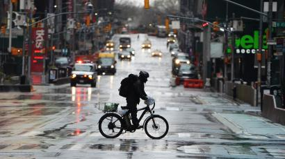 A delivery person on an electric bike rides across a mostly-empty wet street in New York at the start of the pandemic..