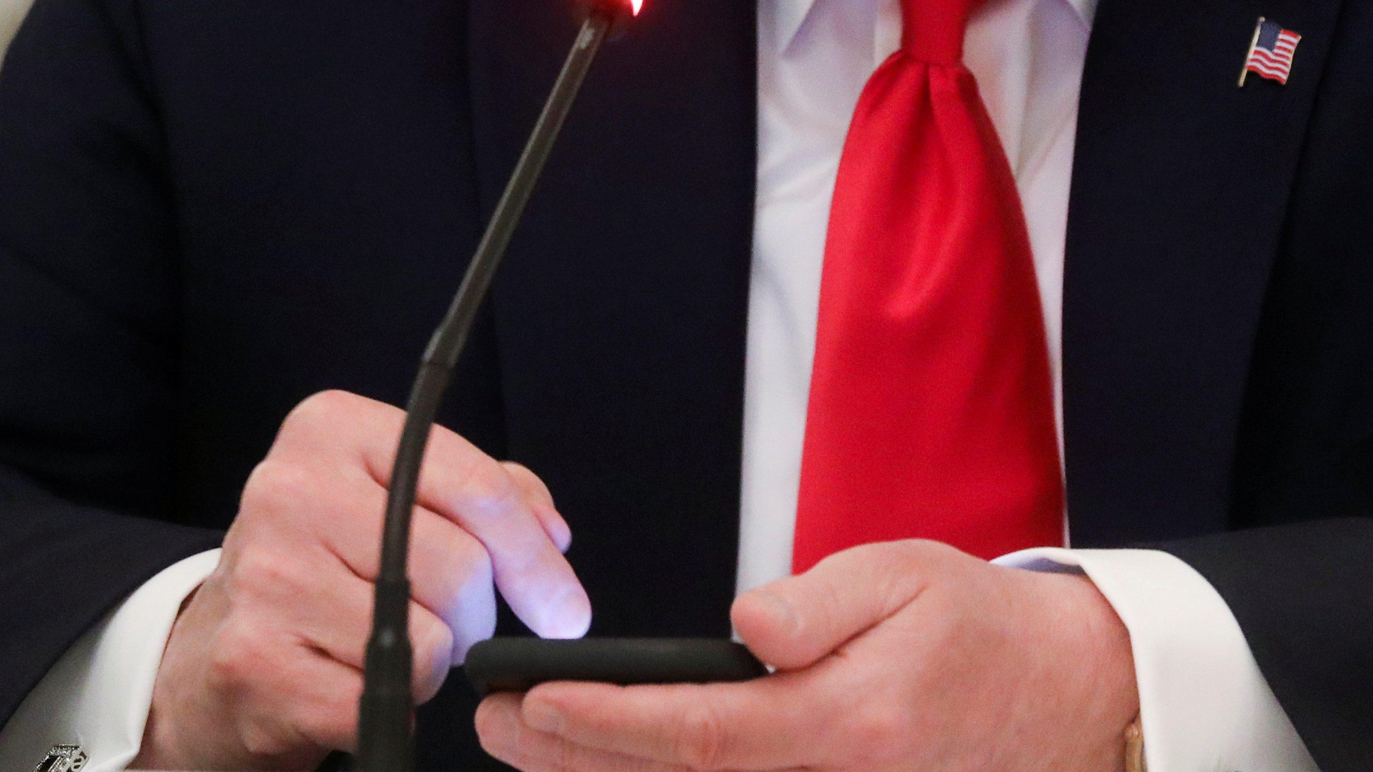 A close-up photograph of Donald Trump using a cellphone.