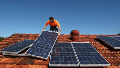 Solar system installer Bywater adjusts new solar panels on the roof of a house in Sydney