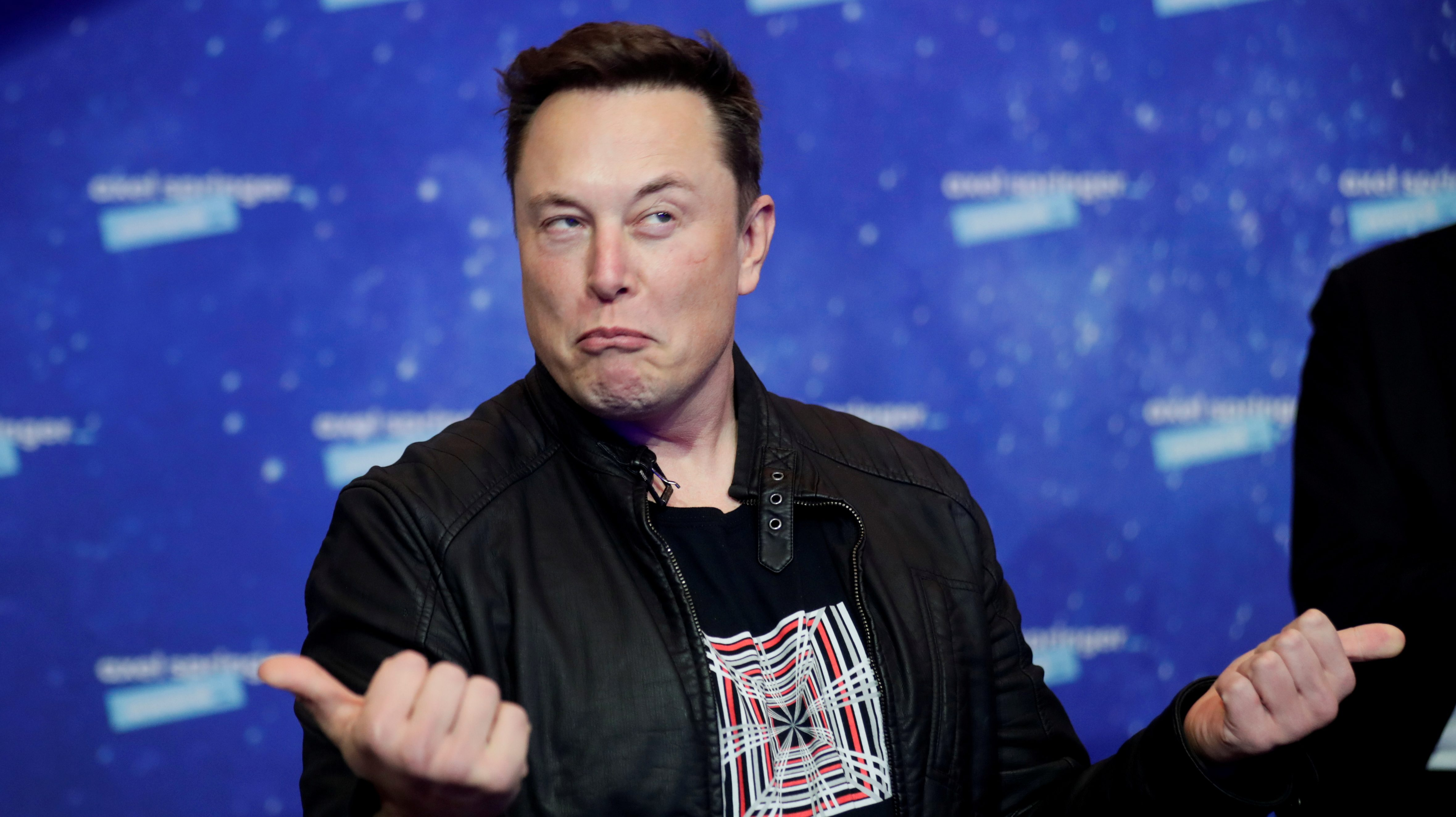 Elon Musk makes a bemused expression similar to a grimace and points his thumbs out while wearing a black t-shirt and black jacket while at an event in Berlin, Germany.