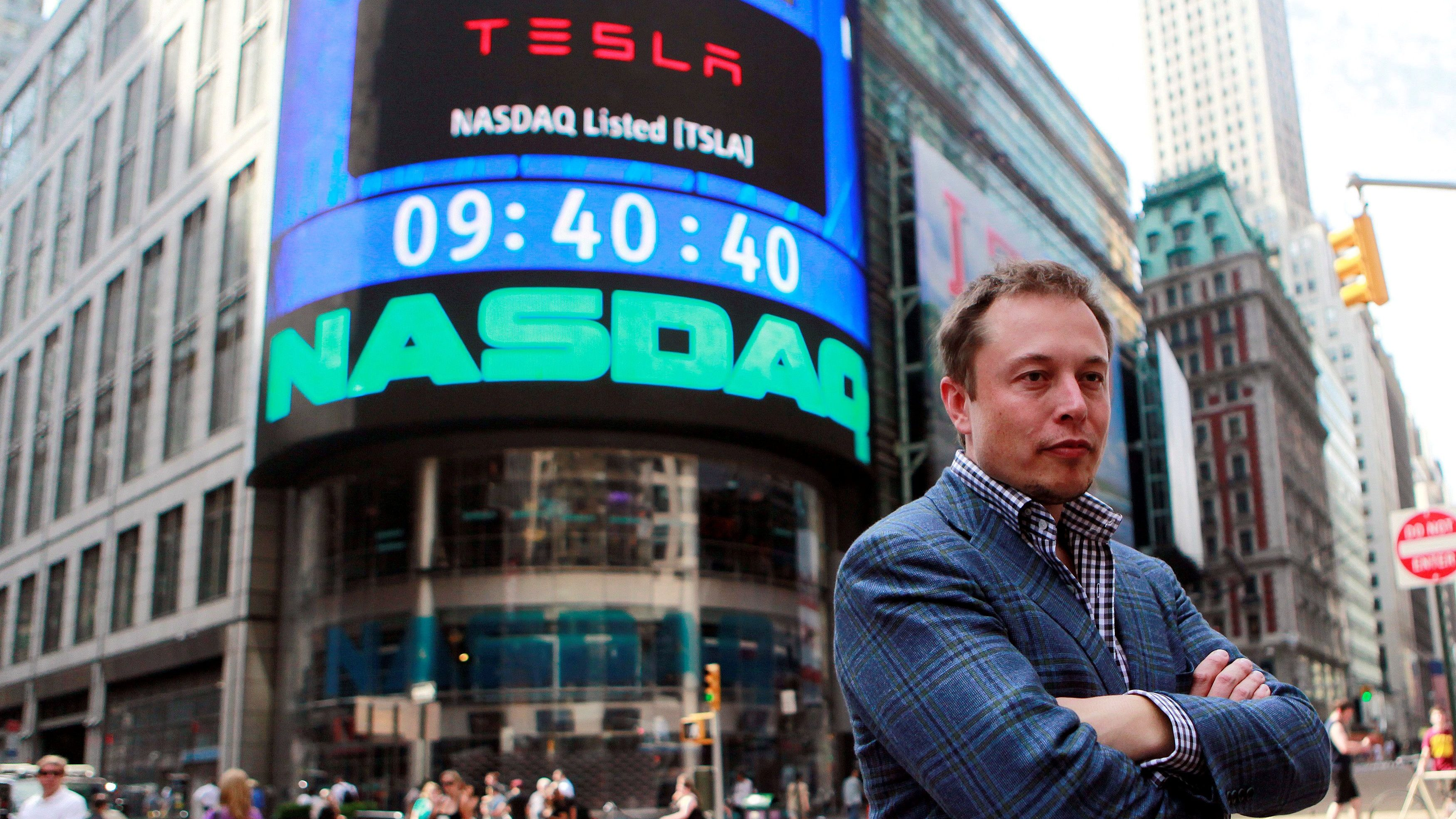 Elon Musk stands with his arms crossed in front of a New York City building with a sign announcing Tesla's listing on the Nasdaq.