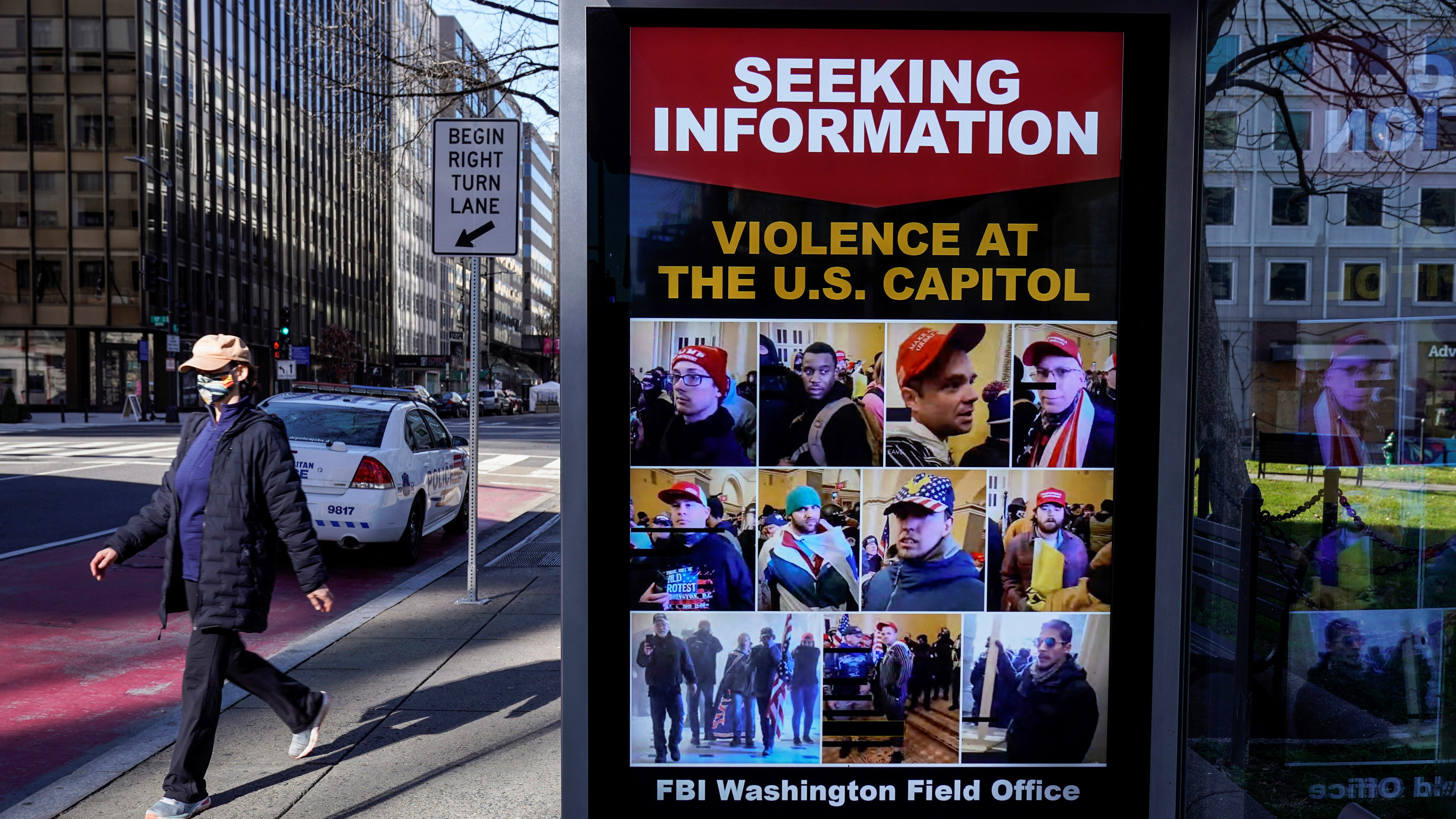A pedestrian walks past a sign at the bus stop from the FBI seeking information on supporters of U.S. President Donald Trump who stormed the U.S. Capitol