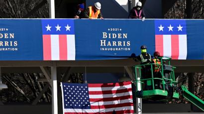 Workers place Biden-Harris inauguration banners on the inaugural parade viewing stand.