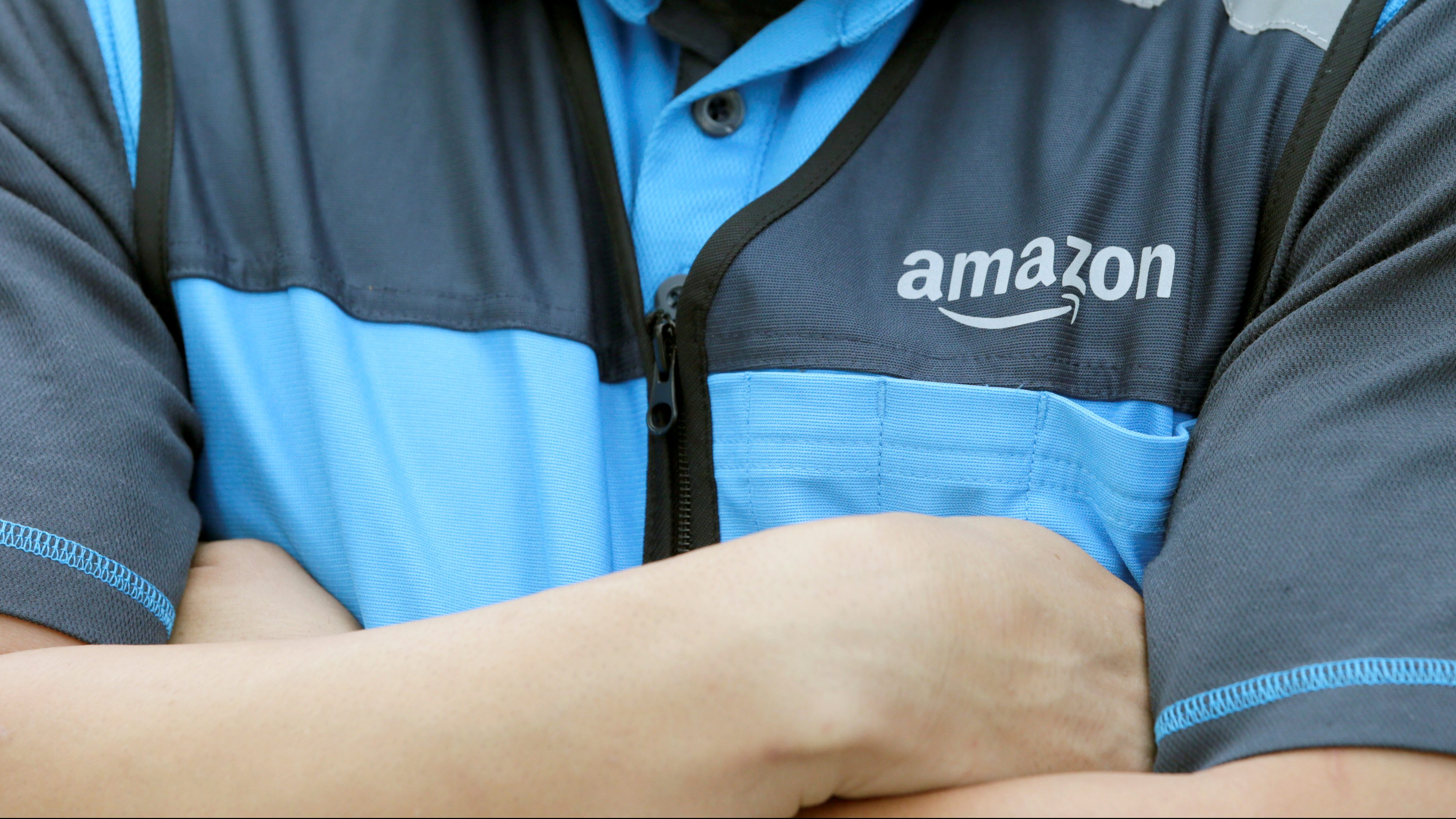 A close-up shot of an Amazon employee's shirt as he stands with his arms crossed