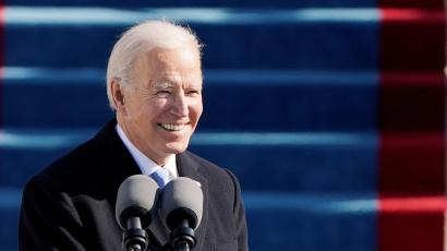 U.S. President Joe Biden smiles as he speaks into two large microphones during the 59th Presidential Inauguration in Washington, U.S., January 20, 2021. In the background is bright blue carpeted steps. Biden is wearing a black jacket, white shirt and grey tie.