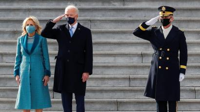 Joe Biden stands on the marble steps of the US Capitol between a saluting marine and First Lady Jill Biden.
