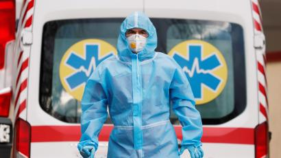 A medical worker wearing protective gear stands next to an ambulance.
