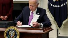 US president Joe Biden signs an executive order as part of plans to fight the pandemic on January 21, 2021.