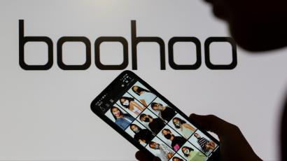 A woman poses with a smartphone showing the Boohoo app in front of the Boohoo logo in this illustration taken September 30, 2020