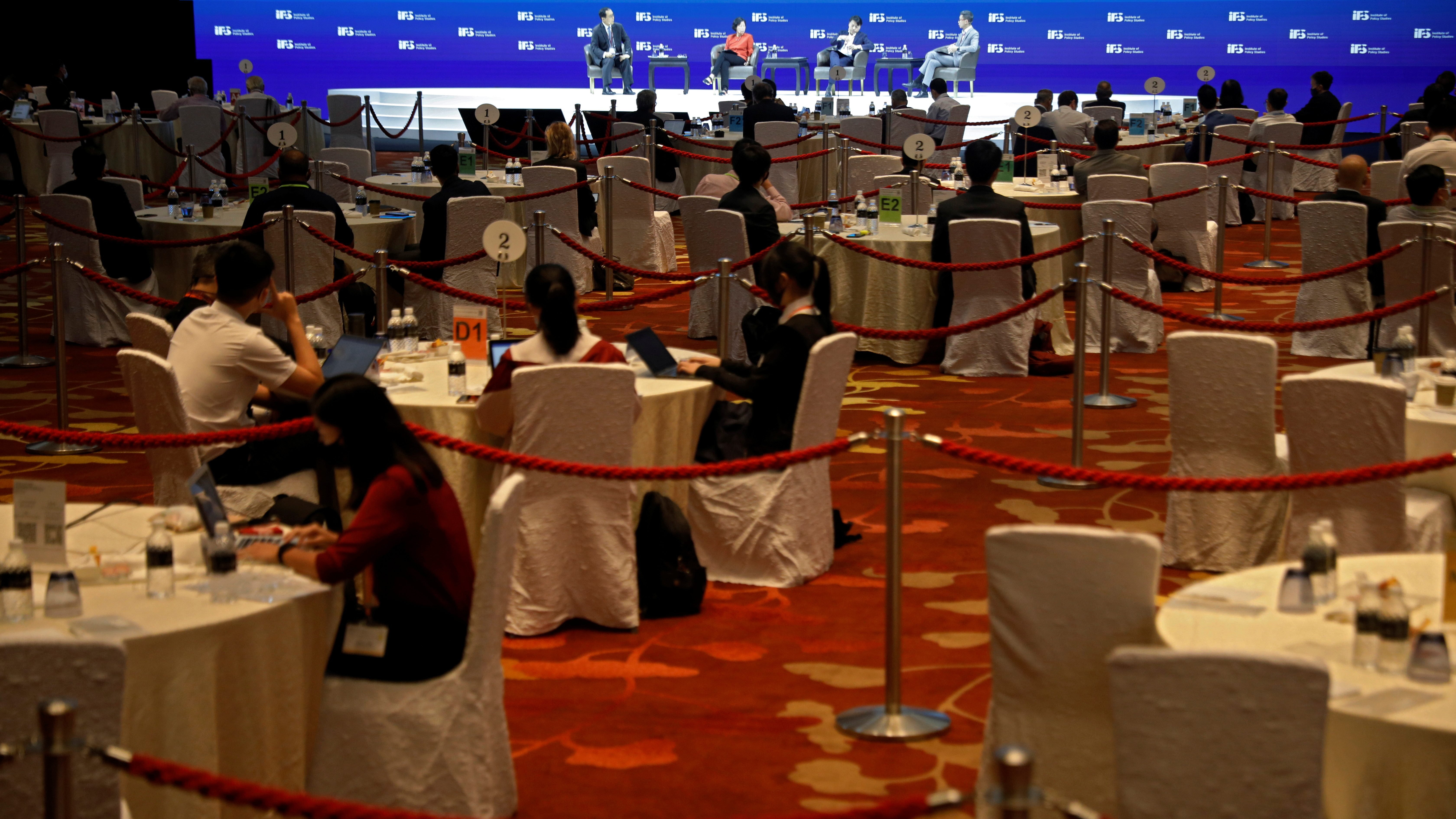 Attendees sit apart at social distanced tables segregated by ropes, during a conference held by the Institute of Policy Studies at Marina Bay Sands Convention Centre in Singapore January 25, 2021. Picture taken January 25, 2021. REUTERS/Edgar Su