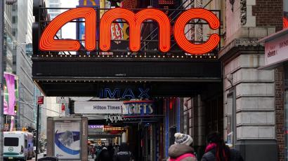 A neon AMC theater sign is pictured while someone walks past wearing a bright red backpack.