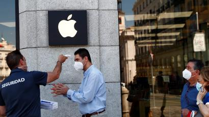 A man wearing a protective mask gets his temperature taken before entering an Apple store, amid the coronavirus disease (COVID-19) outbreak, in Madrid, Spain last summer.