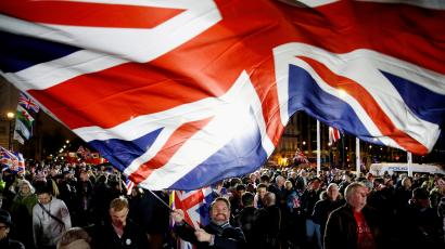 A man waves a British flag to celebrate Brexit.