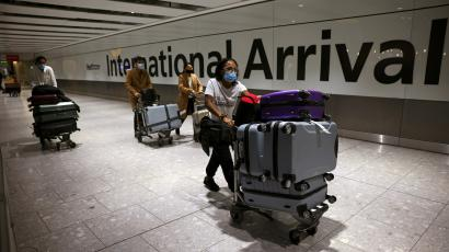 Travellers walk through the arrivals area at Heathrow