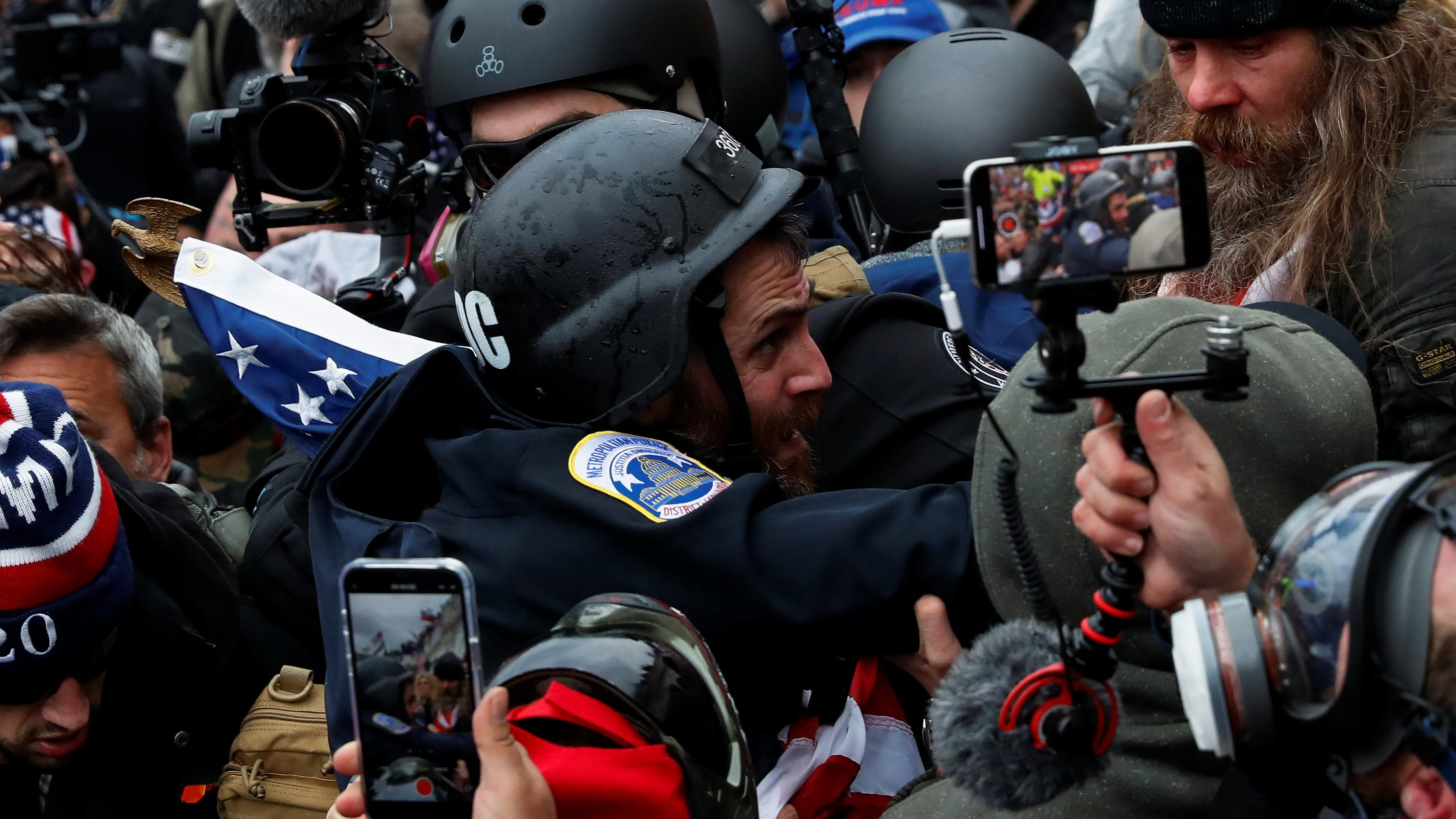 Pro-Trump protesters clash with police and pull out their phones to create videos and take photos during a riot to contest the certification of the 2020 U.S. presidential election results at the U.S. Capitol Building in Washington, U.S, January 6, 2021.