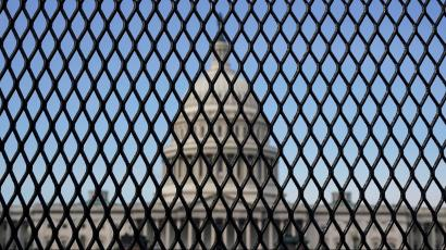 The US Capitol building is seen through a temporary security fence.