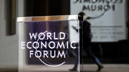A person passes by a World Economic Forum logo in Davos