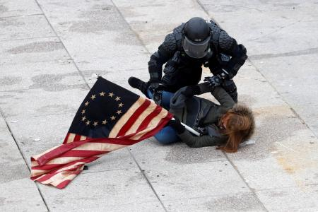 A police officer detains a pro-Trump protester as mobs storm the U.S. Capitol, during a rally to contest the certification of the 2020 U.S. presidential election results by the U.S. Congress, at the U.S. Capitol Building in Washington, U.S, January 6, 2021.