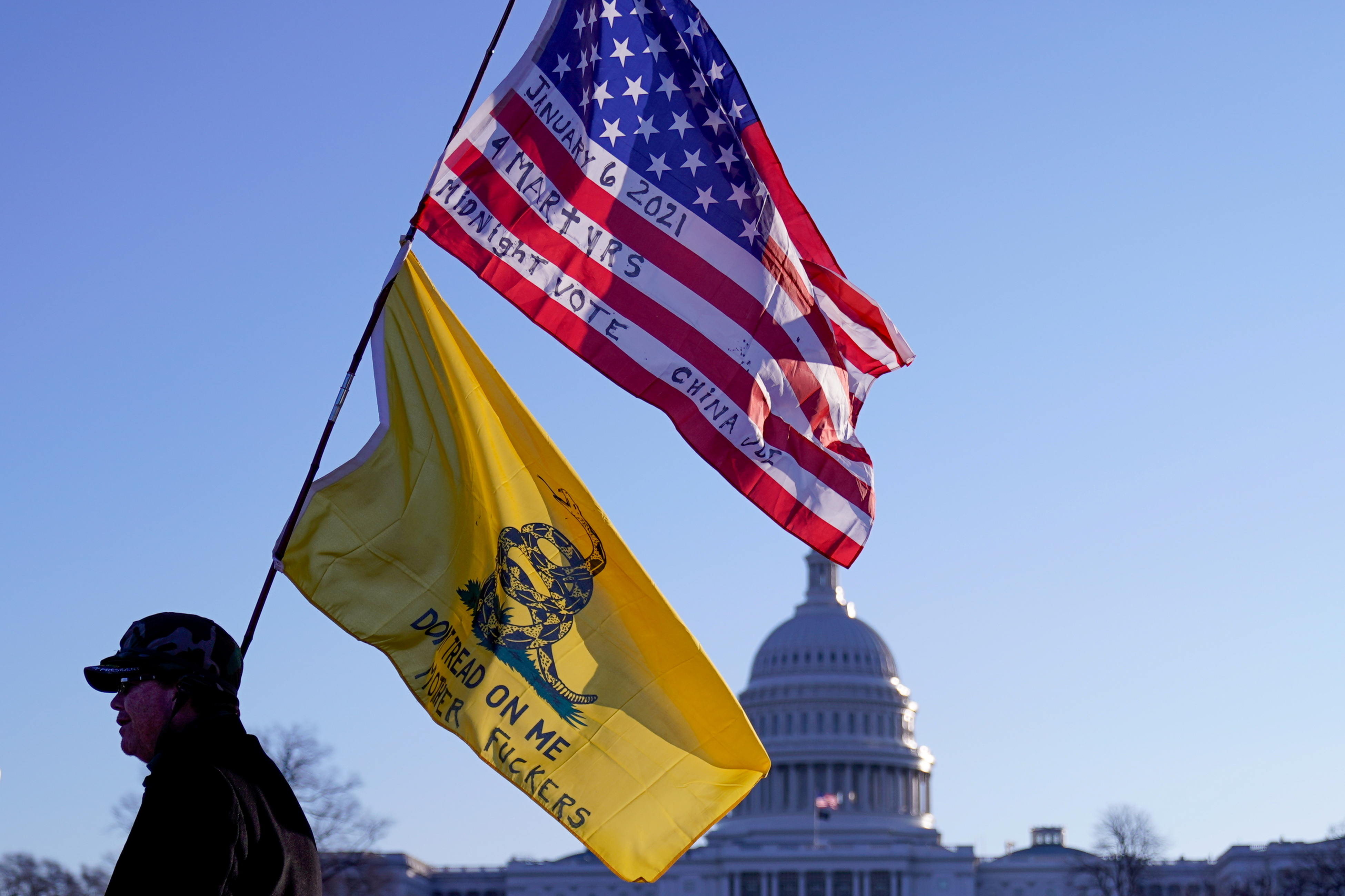 A man walks with a Gadsden and American flags outside the U.S. Capitol, a day after supporters of U.S. President Donald Trump occupied the U.S. Capitol Building in Washington, U.S. January 7, 2021. REUTERS/Erin Scott