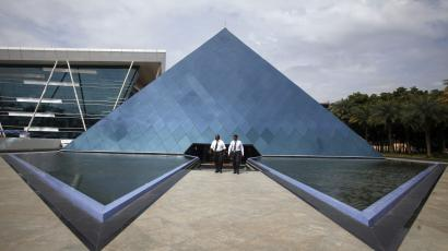 Employees walk in front of a pyramid-shaped building at the Infosys campus in the Electronic City area of Bangalore