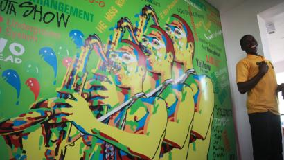 A man stands near a mural on a wall of Nigeria's music legend Fela Kuti during the opening ceremony of a museum in his honour in Lagos in 2012/