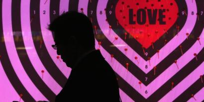 A man using his mobile phone walks past a shop window with signs advertising the upcoming Valentine's Day, at a luxury store in Tokyo
