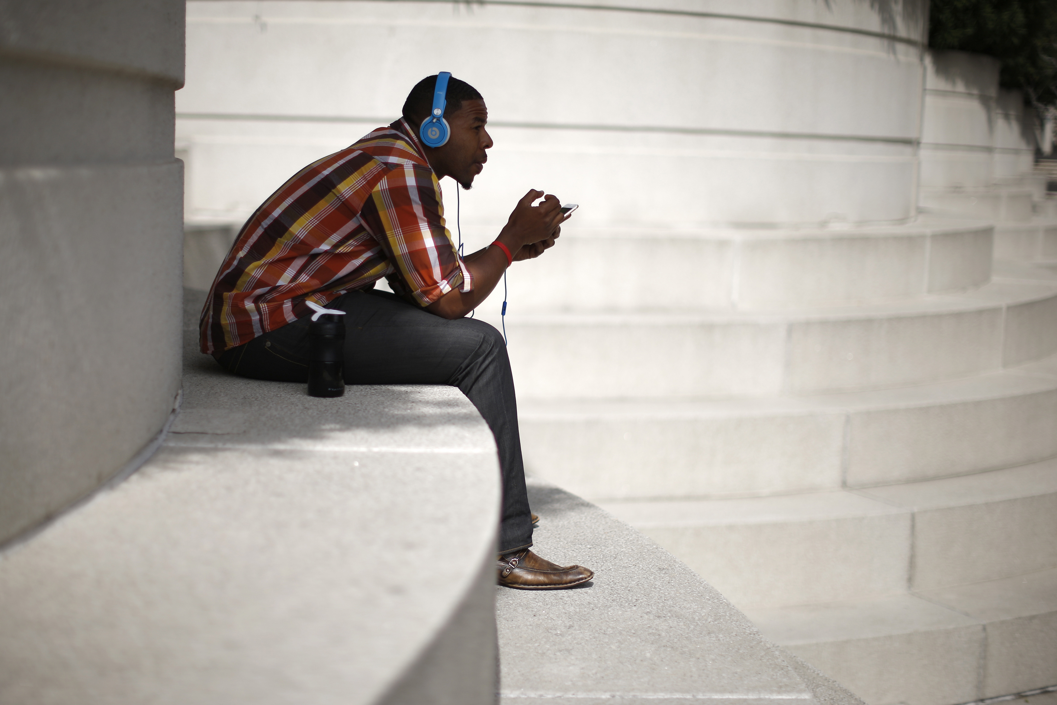 A man with Beats headphones listens to music on an iPhone in Los Angeles