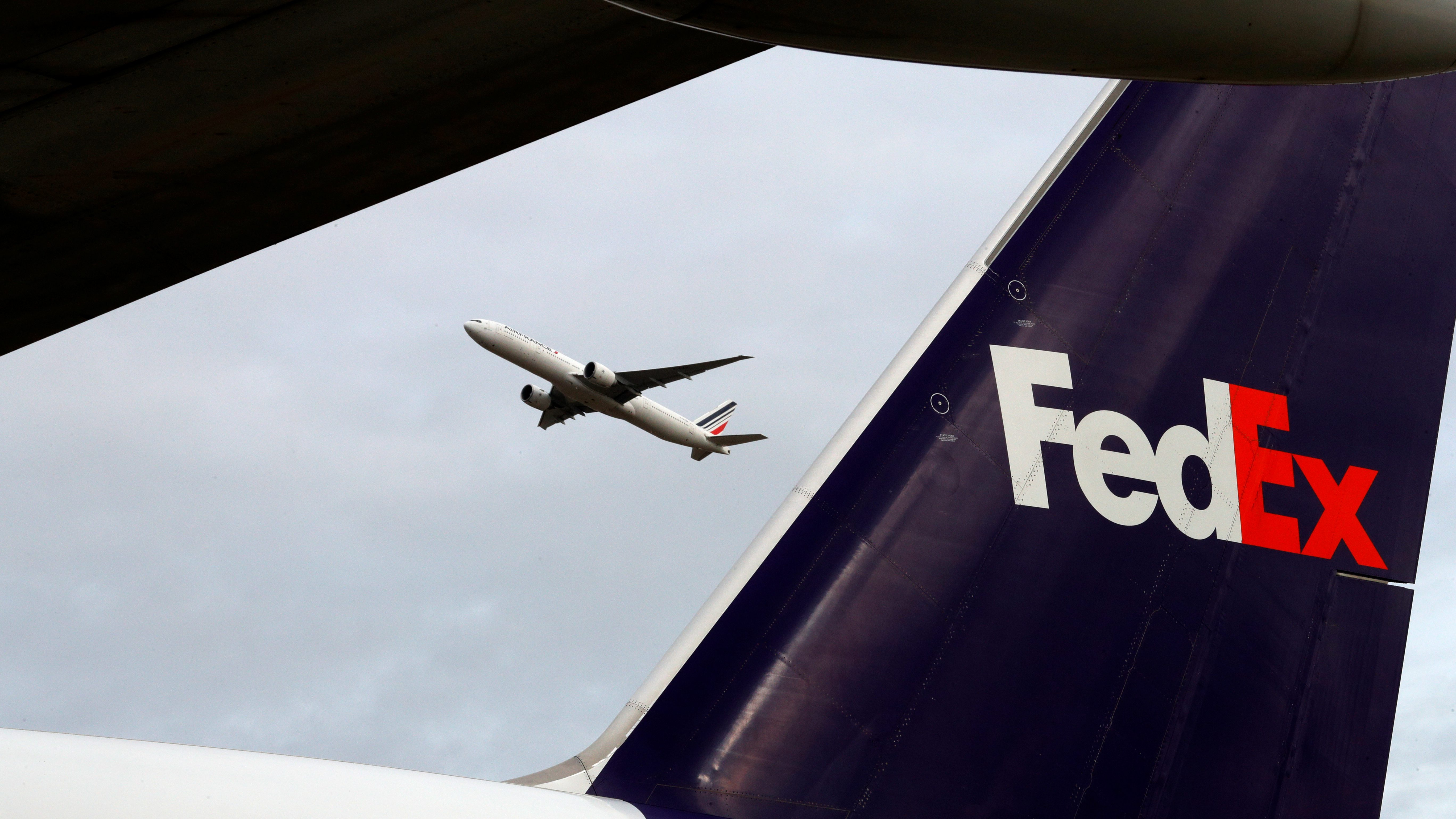 A plane takes off behind the tail of a FedEx plane at the company's hub north of Paris in this 2016 file photo.