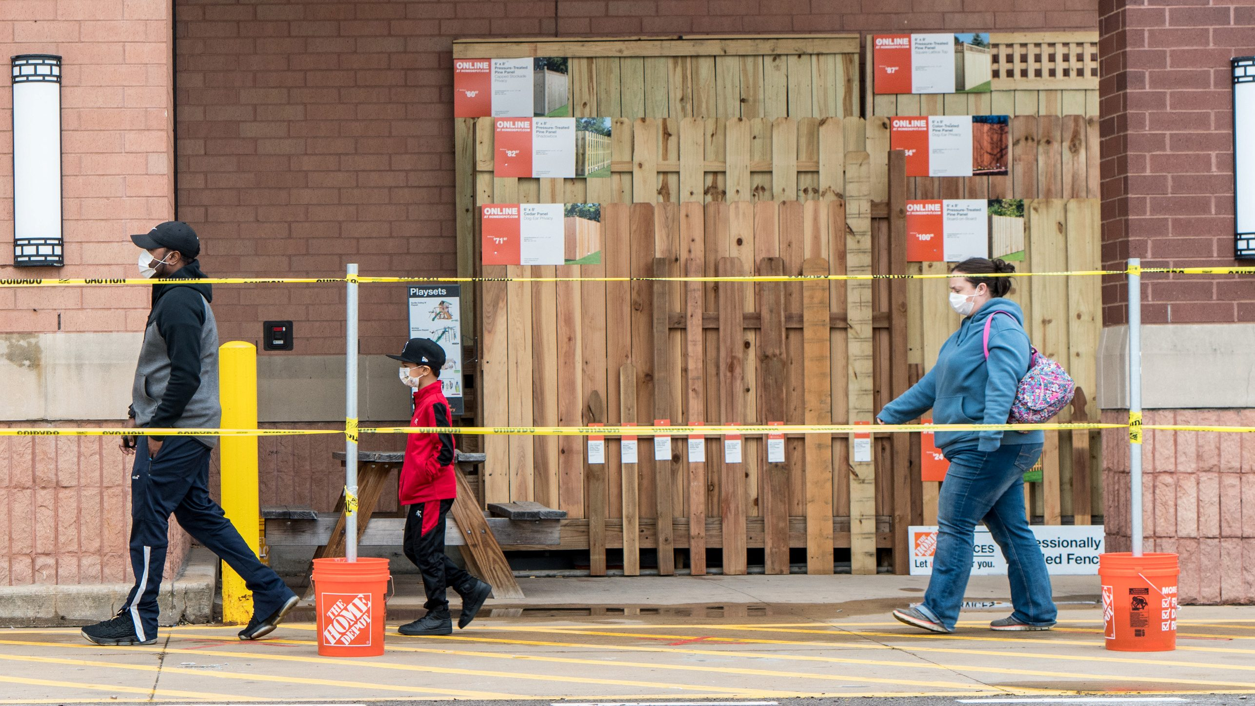 A man, a small boy, and a woman line up outside a Home Depot store while wearing masks and walking several feet apart in front of a fencing display.