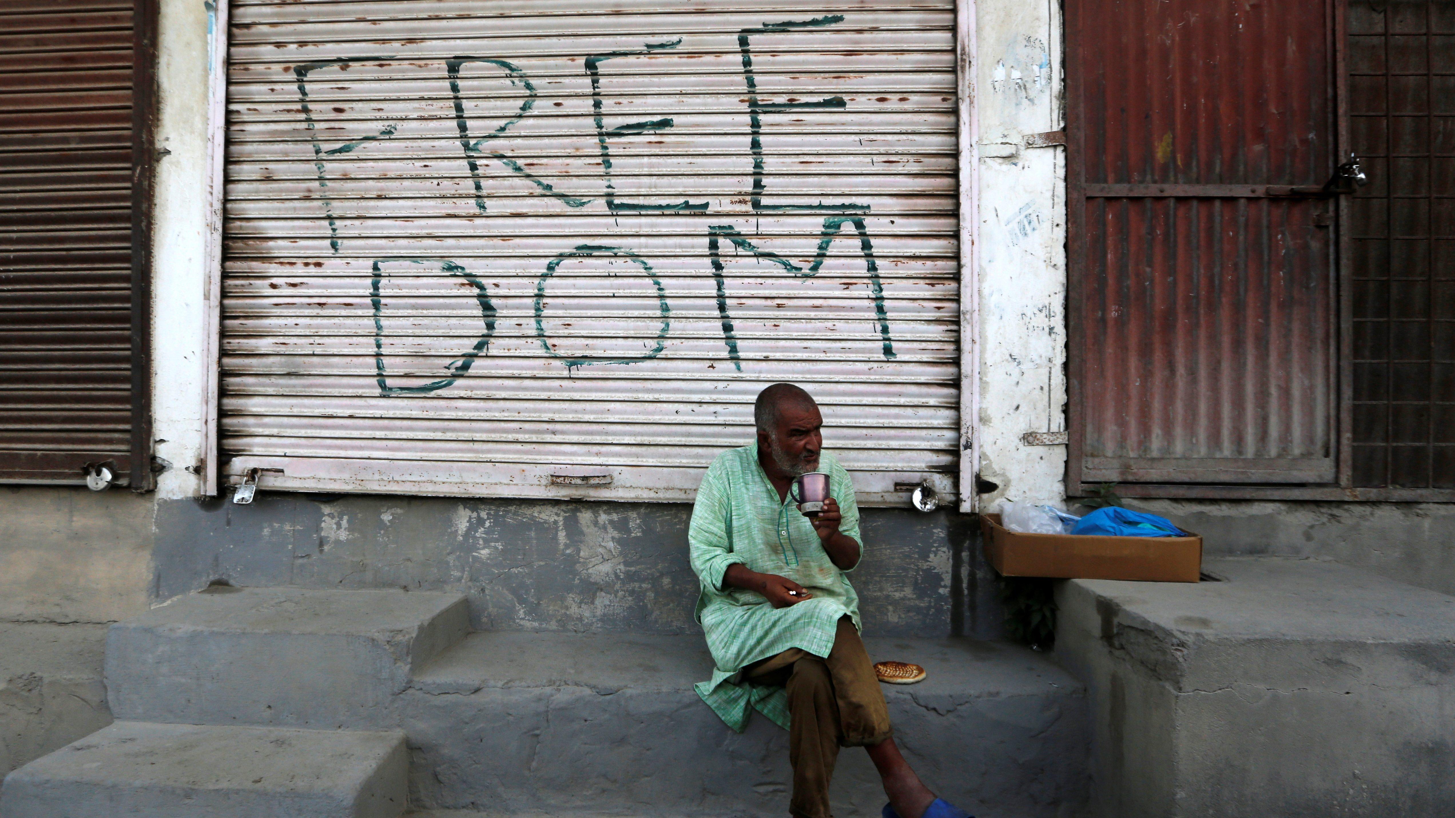Kashmiri man drinks tea in front of a closed shop in Anchar neighbourhood in Srinagar